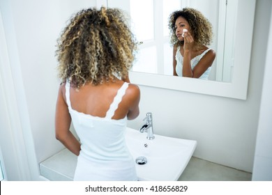 Young woman cleaning her face with sponge in bathroom