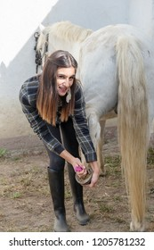 Young Woman Cleaning Her Horse's Hooves