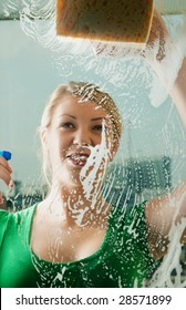 Young woman cleaning her windows with spray and sponge