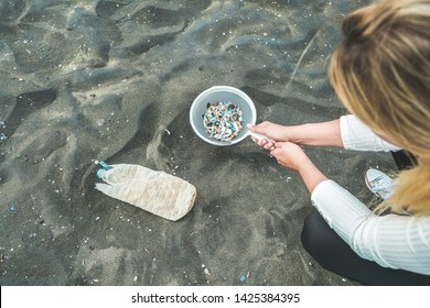 Young woman cleaning microplastics from sand on the beach - Environmental problem, pollution and ecolosystem warning concept - Focus on plastic garbage inside the net