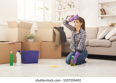Young Woman Cleaning New Appartment With Rag And Detergent In Living Room Full Of Moving