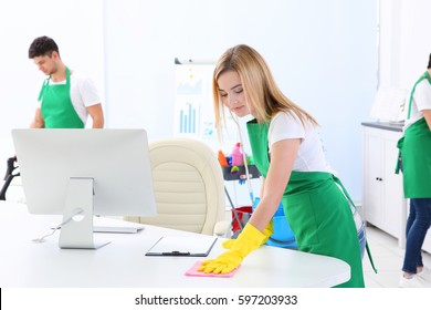 Young woman cleaning office table