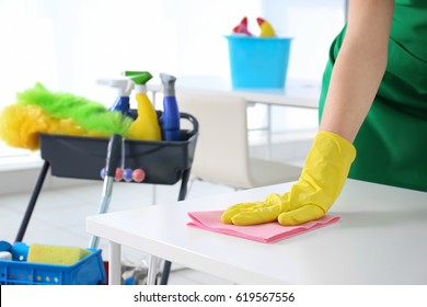 Young woman cleaning office table, closeup