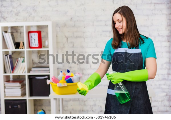 Young woman - Cleaning staff spraying detergent on the sponge, standing in a modern room. Professional cleaning of apartments