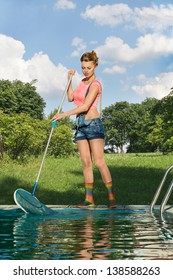 Young woman cleaning swimming pool