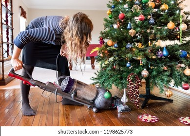 Young woman cleaning with vacuum cleaner, vacuuming under Christmas Tree needles with New Years ornaments on hardwood wooden floor