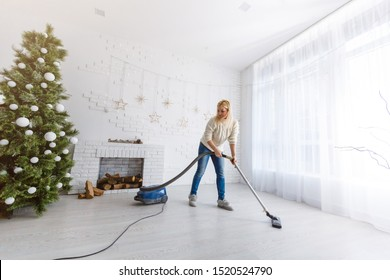 Young woman cleaning with vacuum cleaner hardwood floor after New Year needles from Christmas tree in hall room near entrance door