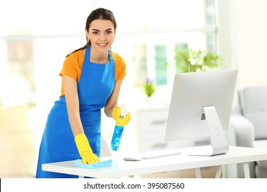 Young woman cleaning workplace with computer monitor in the office