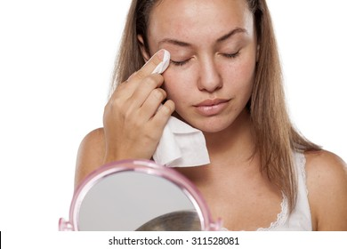young woman cleans her eyelids with wet wipes