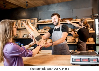 Young woman client buying bread at the bakery shop with handsome male sellers