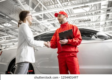 Young woman client shaking hands with auto mechanic in red uniform having a deal at the car service