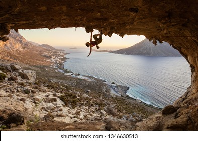 Young woman climbing in cave at sunset, Kalymnos Island, Greece