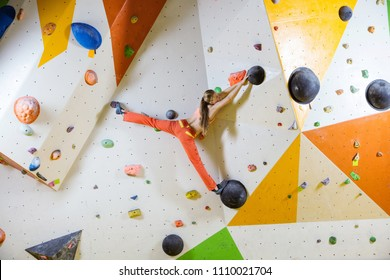 Young woman climbing challenging bouldering route. In indoor climbing gym.