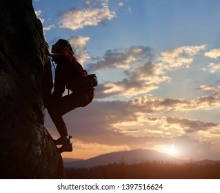 Young woman climbing high up on rock at sunset in mountains. Cloudy sky on background. Side view. Copy space for text. Difficult ascent to mountain top. Extreme, hiking, overcoming obstacles concept.