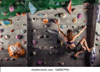 Young woman climbing up on practice wall in gym