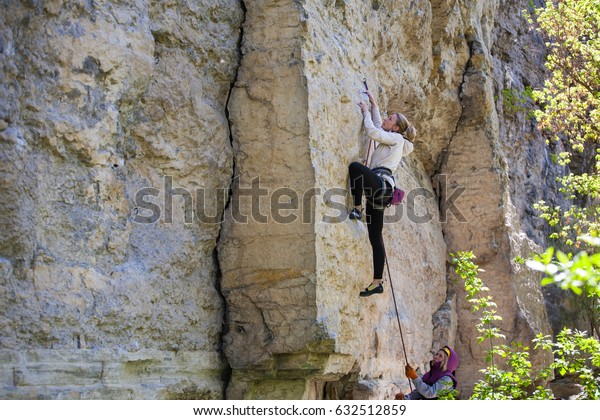 A young woman is climbing on the rocks, active rest on nature.