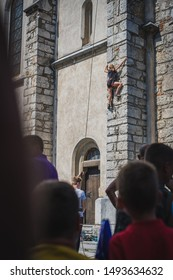 Young woman climbing on the wall of a church. Athlete climbing on a church bell tower as a part of a fair display. People watching her climb