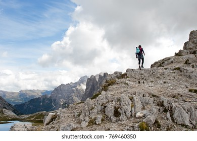 Young woman climbing a rocky slope in the heart of the mountain