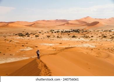 Young woman climbing the Sossusvlei dunes, Namibia