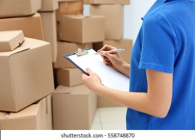 Young woman with clipboard at warehouse, closeup