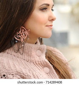 Young woman close up portrait, pink boho style dreamcatcher earrings