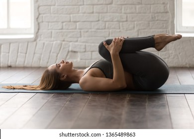 Young woman with closed eyes practicing yoga, beautiful girl in grey sportswear, pants and bra lying in Knees to Chest pose, doing Apanasana exercise, working out at home or in yoga studio