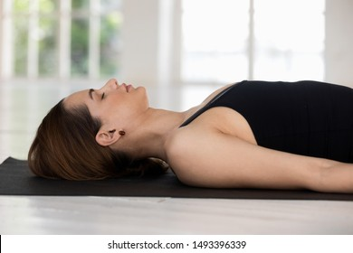 Young woman with closed eyes practicing yoga, doing Savasana exercise, meditating, relaxing in Corpse pose, sporty girl wearing black sportswear working out at home or in yoga studio close up