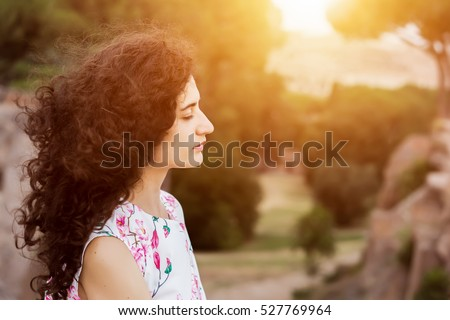 Young woman with closed eyes relaxing in summer nature landscape. Finding body and mind balance. Portrait of young relax woman with curly hair. Serenity, mindfulness, peace mind, stress free concepts