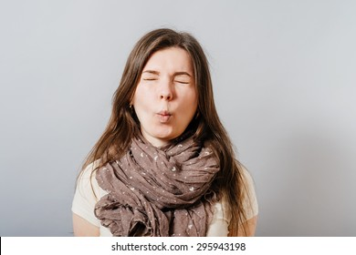 Young woman closed her eyes, a grimace. On a gray background.