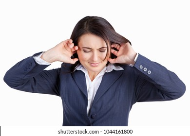 Young woman closes her ears with hands. Sharp pain in ears, feeling of pressure in the ear. Brunette in business suit isolated on white background