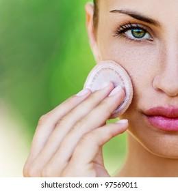 young woman closeup applying foundation