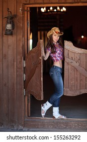 A young woman in clothes cowboy standing in the doorway of the saloon