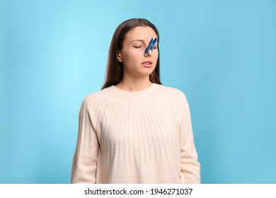 Young woman with clothespin on light blue background. Runny nose concept