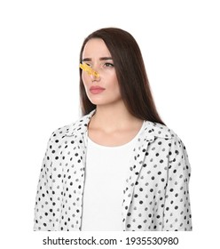Young woman with clothespin on white background. Runny nose concept
