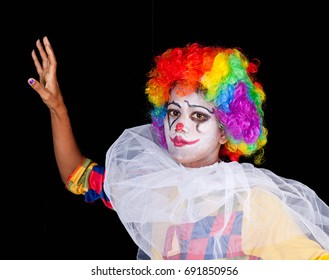 young woman as clown on black background