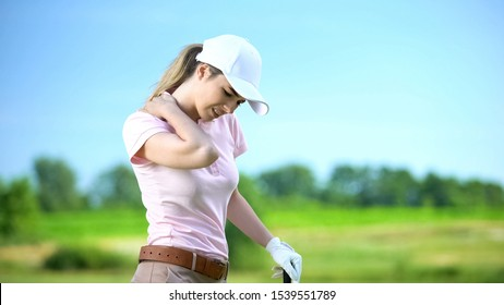 Young woman with club playing golf, suffering sharp shoulder pain, sports trauma