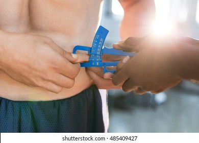 Young woman coach is measuring his body fat of sporty man with calipers.