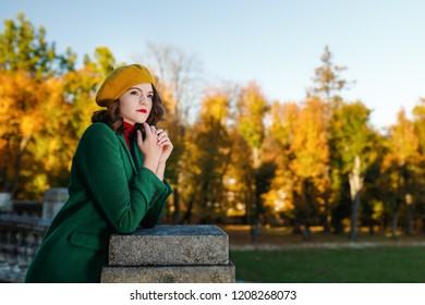 Young woman in coat with beret in autumn park