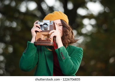 Young woman in coat with beret and vintage camera in autumn park