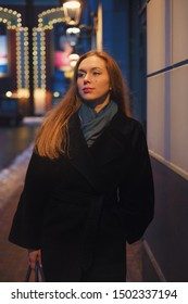 Young woman in a coat on the street under the lights