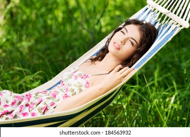 Young woman in cocktail dress relaxing in a hammock over sunny background.