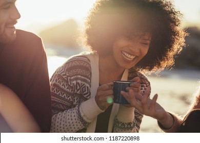 Young woman with coffee cup laughing while sitting with friends at the beach. Cheerful friends at the beach at sunset.