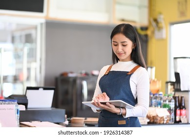 Young woman coffee shop owner wearing apron holding digital tablet ready to receive orders.