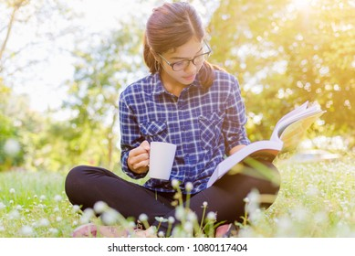 young woman with coffee sitting on the grass and reading a book in the park