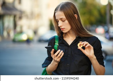 young woman with coin bitcoin and smartphone in hand on the background of old city street.