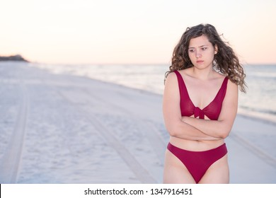 Young woman cold shivering sad crossed arms in red bikini swimsuit standing in beach sunrise or sunset in Florida panhandle with calm ocean and sand