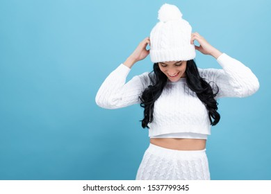 Young woman in a cold weather winter outfit on a blue background