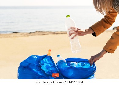 Young woman collecting plastic trash from the beach and putting it into blue plastic bags for recycle. Cleaning and recycling concept.