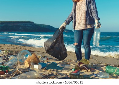 Young woman collects plastic garbage in a garbage bag on the sandy beach of the sea. Spilled garbage on the beach. Empty used dirty plastic bottles. Environmental pollution shore the Black Sea