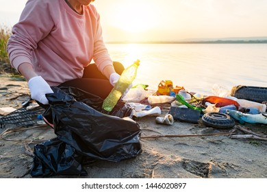 Young woman collects plastic garbage in a garbage bag, household rubbish on the sandy beach of the sea at sunset. Spilled garbage on beach. Empty used dirty plastic bottles. Environmental pollution